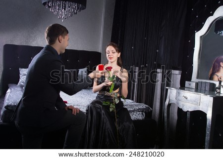 Kneeling Young Man Offering a Jewelry Gift to his Happy Pretty Girlfriend While at the Bedroom. - stock photo