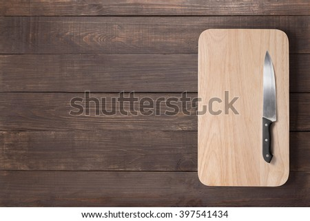 Knife and cutting board on the wooden background.