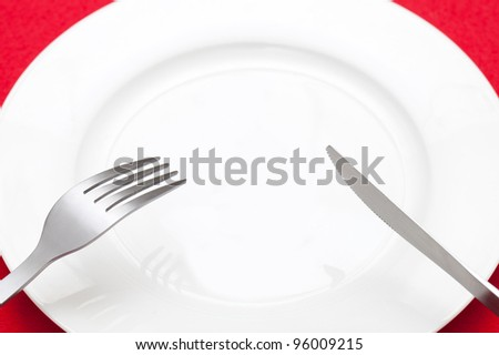 knife and fork above empty plate - stock photo