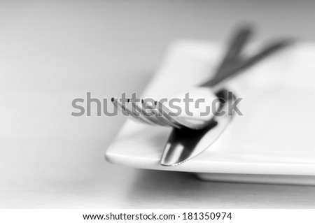 Knife and fork cutlery with a white place in very shallow focus in black and white - stock photo