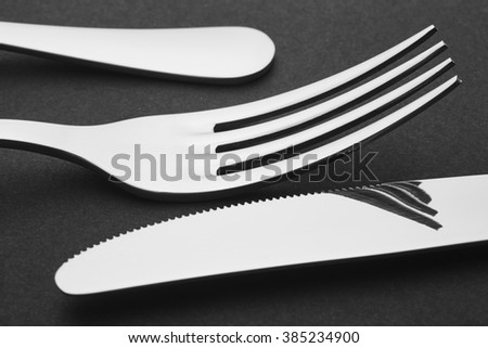 Knife and fork detail over a black background. Cutlery. Horizontal - stock photo
