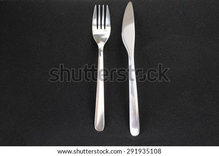 Knife and fork isolated on black background  - stock photo