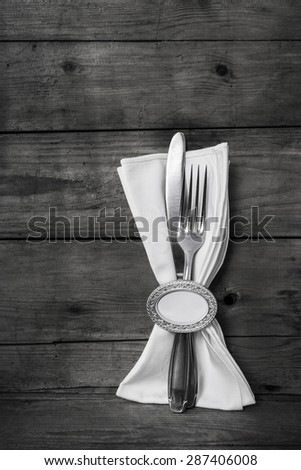 Knife and fork on grey elegant wooden background with a white napkin. - stock photo