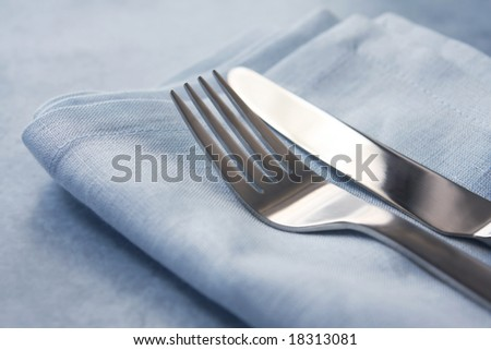 Knife and fork on pastel blue napkin.  Soft-focus, shallow depth of field.