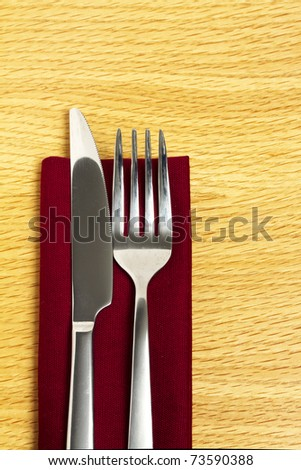 Knife and fork on red napkin - stock photo