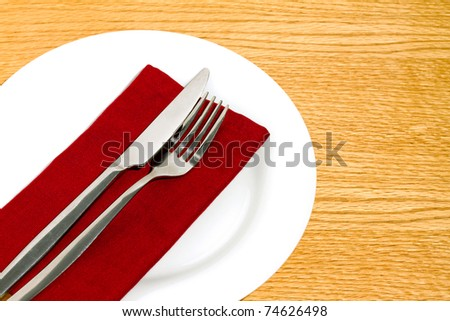 Knife and fork on red napkin on round white plate