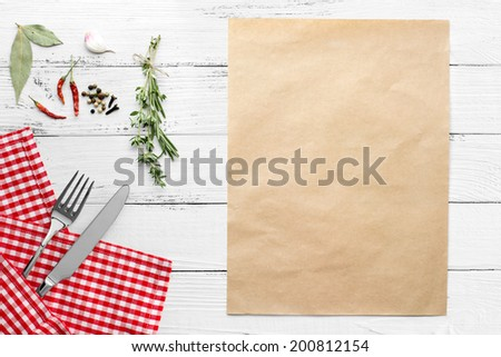 knife and fork on white old vintage wooden table with red checked tablecloth and copyspace. still life backgound - stock photo