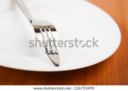 knife and fork on white plate