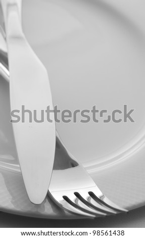 Knife and Fork on White Plate - stock photo