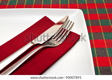 Knife and fork on white square plate with green and red tablecloth