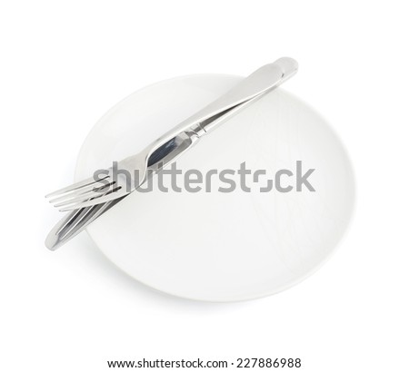 Knife and fork over the empty white ceramic plate isolated over the white background - stock photo