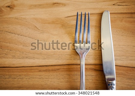 Knife and fork set on a wooden  table - stock photo