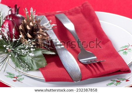 Knife and fork with napkin on Christmas plates - stock photo