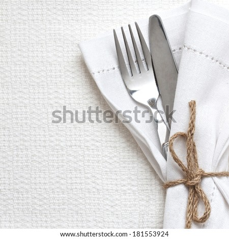 Knife and fork with white linen with up with string