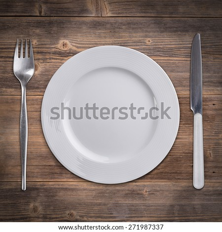 Knife and fork with white plate on a rustic wooden surface