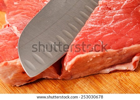 Knife and meat on chopping board