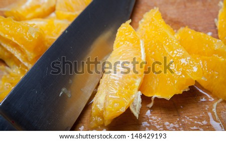 knife chopping oranges into segments on a wooden board. cooking with fruit.