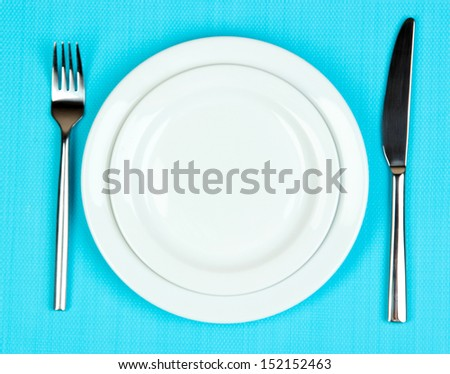 Knife, color plate and fork, on color background