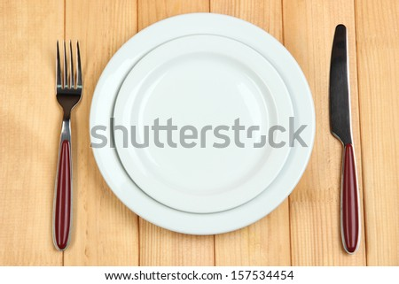 Knife, color plate and fork, on wooden background