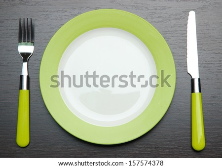 Knife, color plate and fork, on wooden background - stock photo