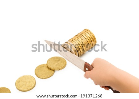 Knife cutting a pile of coin. Concept of budget cuts, savings, recession - stock photo