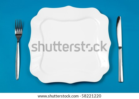 Knife, figured white plate and fork on blue background - stock photo