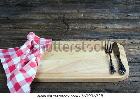 knife fork and napkin plaid on a cutting board on wooden background - stock photo