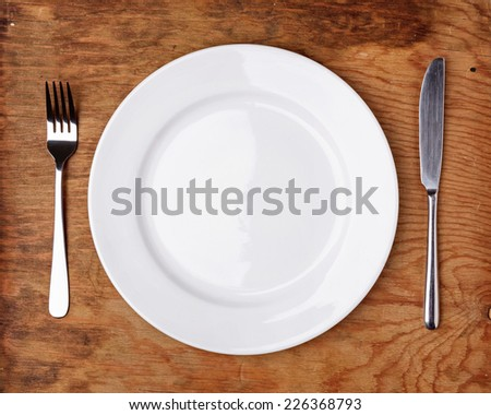 Knife, Fork and plate on wooden table. Top view.
