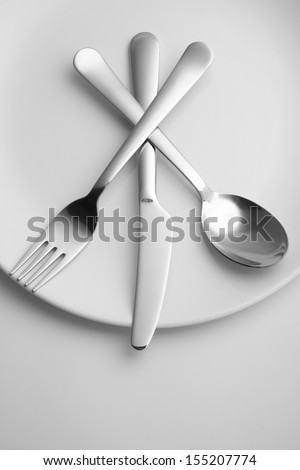 Knife, fork and spoon on white plate, toned image - stock photo