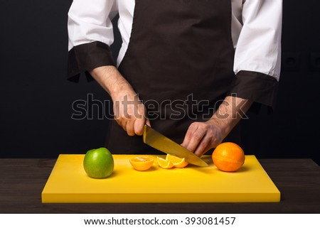 Knife in hand, cut fruit on a cutting board