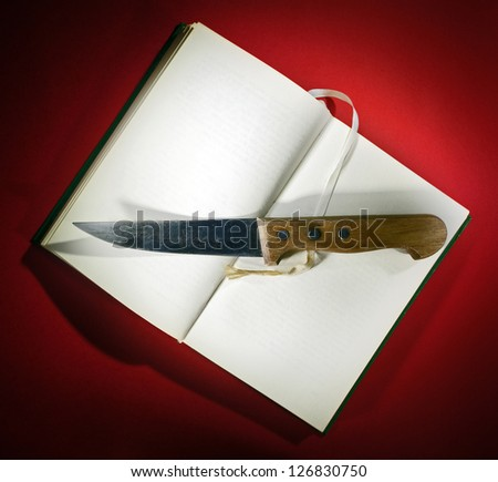 Knife on opened book on red background.