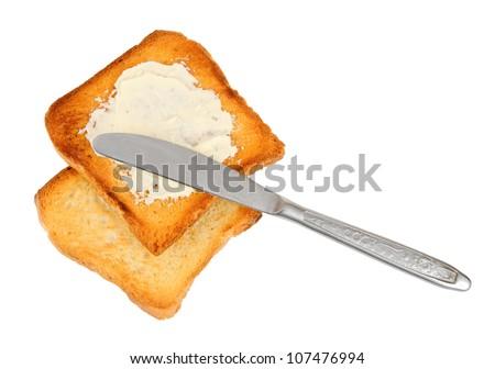 knife on spreaded crispy toasts, over white background - stock photo