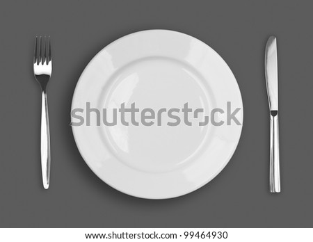 Knife, white plate and fork on gray background - stock photo