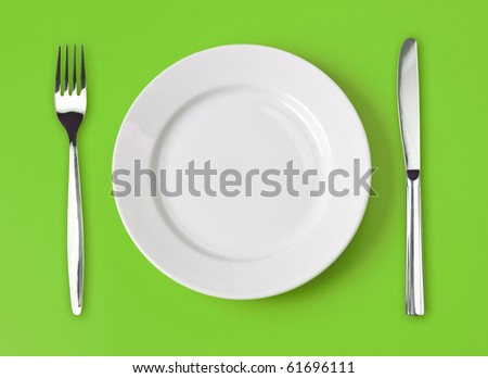 Knife, white plate and fork on green background - stock photo