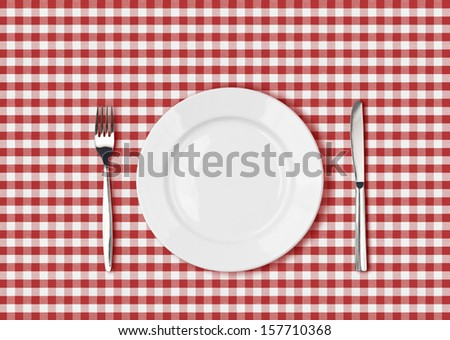 Knife, white plate and fork on red picnic table cloth - stock photo