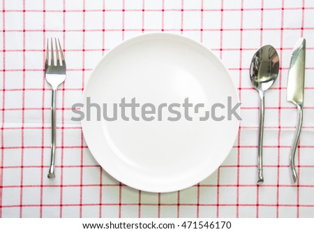 knife white plate and fork spoon on red checked tablecloth