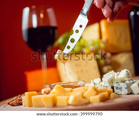 Knife with piece of cheese on a dark table.