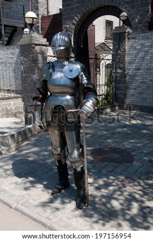 knight in the ancient metal armor standing near the stone wall - stock photo