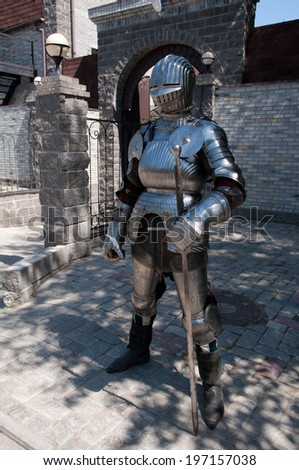 knight in the ancient metal armor standing near the stone wall and the entrance to the castle - stock photo