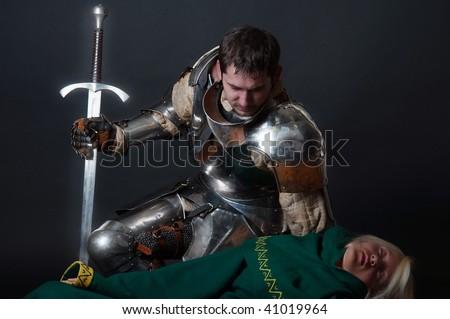 Knight looking at dead assassin - stock photo