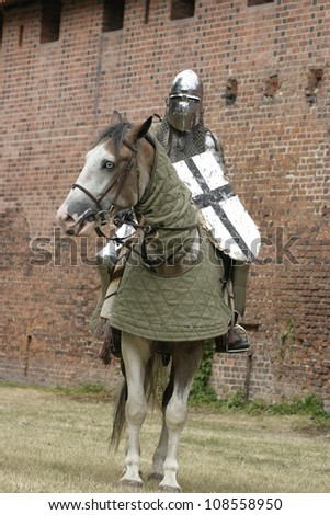 Knight on horse with weapon in hand.