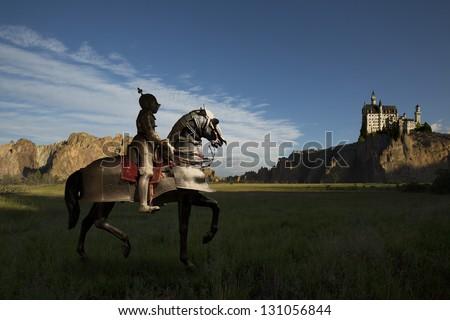 Knight on horseback, castle in distance atop rocks - stock photo