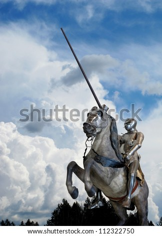 Knight on horseback, with armor and lance, against clouds - stock photo