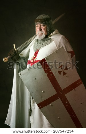 Knight Templar posing with sword in a dark background - stock photo