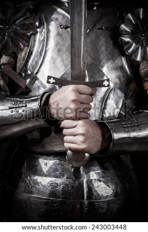knight wearing armor and holding two-handed sword - stock photo