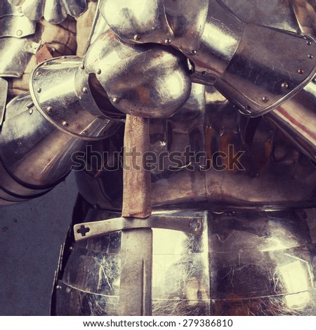 knight wearing armor and standing with two-handed sword - stock photo