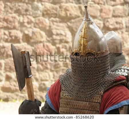 Knights in an armor and with the weapon against a stone wall - stock photo