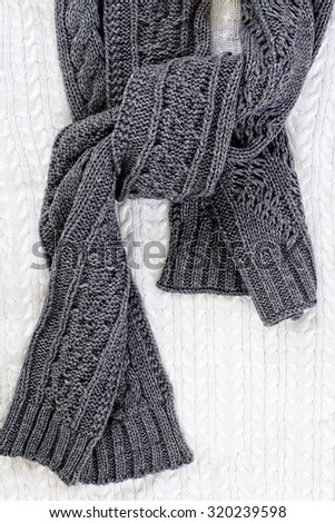 Knit grey winter scarf over a sweater background.  - stock photo