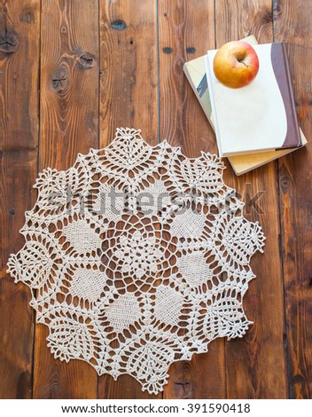 knited openwork crochet doily lying on a wooden table. view from above - stock photo