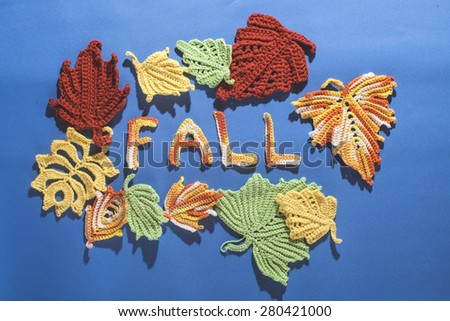 Knitted autumn leaves on blue textile - stock photo